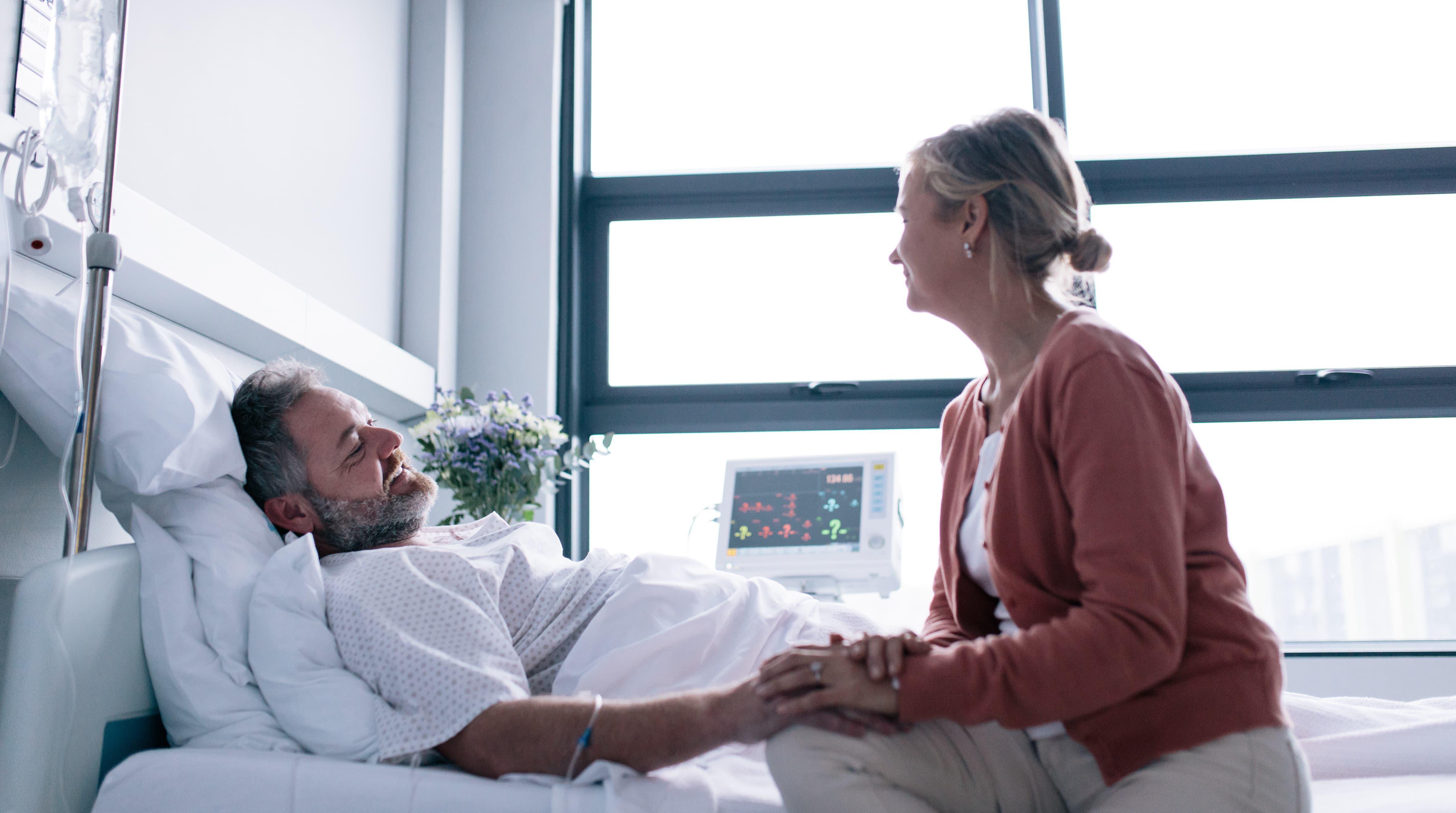 Frau besucht Mann am Krankenbett