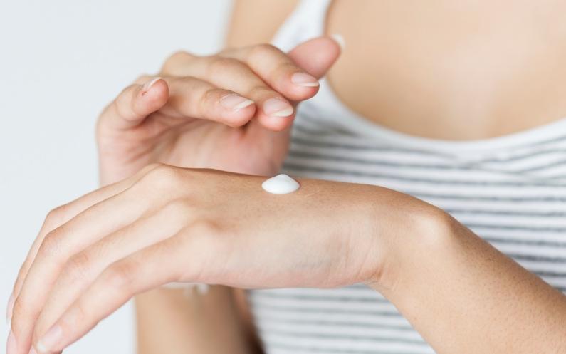 Frau trägt Pflegeprodukt auf die Haut auf.